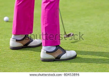 golfer with pink trousers is lining up a putt