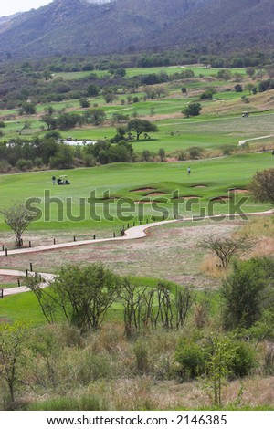 Golfers with a golf cart in the fairway surrounded by bunkers and hazards #2146385