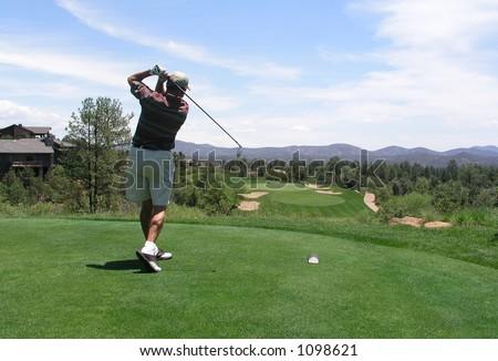 Golfista que golpea la pelota de golf del rectángulo dela te en curso de golf hermoso - stock photo