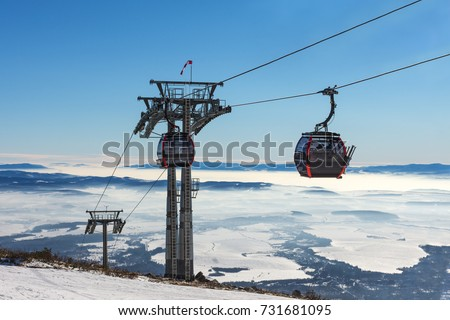 Gondola lift. Cabin of ski-lift in the ski resort in the early morning at dawn with mountain peak in the distance. Winter snowboard and skiing concept #731681095