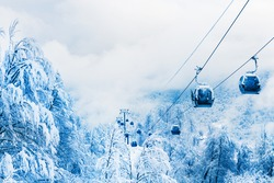 Gondola lift in ski resort in winter mountains during snowfall. Rosa Khutor, Sochi, Russia. Beautiful snow-covered forest, winter landscape