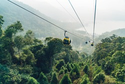 Gondola lifts moving over mountain with green trees in the area of Sun Moon Lake Ropeway in Yuchi Township, Nantou County, Taiwan.