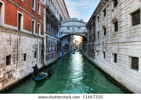 Gondola on small canal passing towards famous Bridge of Sighs (Ponte dei Sospiri) in Venice, Italy.
