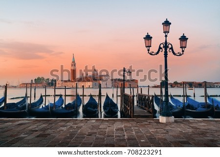 Gondola park in water and San Giorgio Maggiore island in Venice at sunrise, Italy.