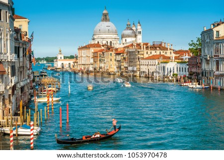 Gondola with tourists sails on the Grand Canal, Venice, Italy. Beautiful sunny view of Venice in summer. Nice panorama of Venice from above. Romantic water trip across Venice on a sunny day.  #1053970478