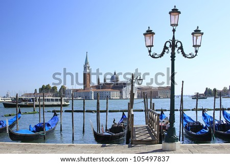 Gondolas and a romantic lantern frames the view on the lagoon and the island of San Giorgio Maggiore, from St. Mark's Square, Venice, Italy