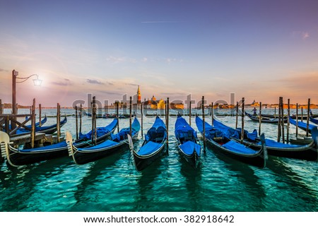 Gondolas in Venice sunset view with San Giorgio Maggiore church from San Marco square in Italy. Intentional motion blur.