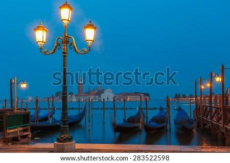 Gondolas moored by Saint Mark square with San Giorgio di Maggiore church in the background at twilight in Venice lagoon, Italia