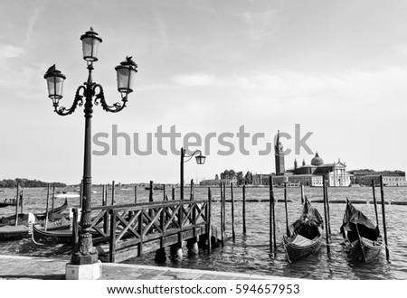 Gondolas moored by St Mark's Square with Church of San Giorgio Maggiore in the background in Venice  #594657953