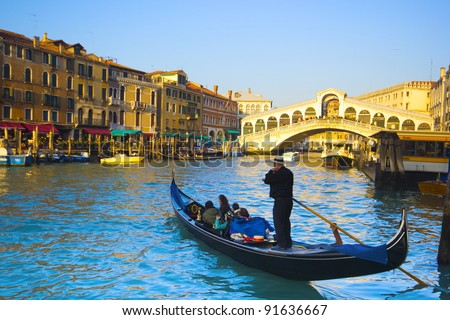 gondolas on the Grand Canal in Venice. Rialto Bridge on background. Sunset