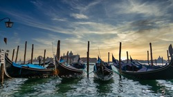 Gondolas tied up on the outskirts of the city of Venice with a sunset in the background