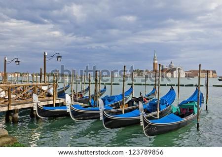 Gondolas waiting for tourists near Piazza San Marco in Venice. View with dramatic sky toward San Giorgio Maggiore.