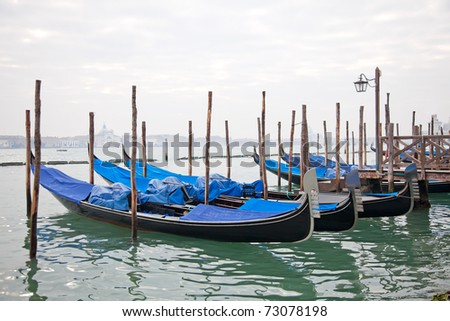Gondolas with blue cover in Venice at the pier