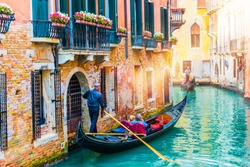 Gondolier carries tourists on gondola in canal of Venice, Italy. Traditional Venice gondola on famous canal. Beautiful Venice view.