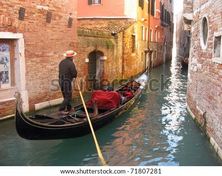 gondolier in a gondola along a canal through the houses of Venice