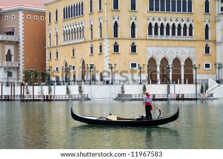 Gondolier navigates the venetian canal