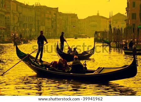 Gondolier navigates the venetian canal in sunset light - stock photo