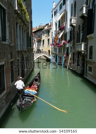 Gondolier paddling his gondola through a small channel in Venice, Italy.
