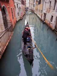 Gondolier sails through the canals of Venice. Happy sea man carries a gondola around Venice, Italy.