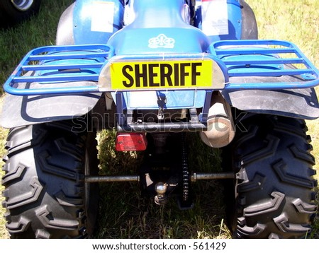 Gone are the days of the Sheriff on horseback. Now mechanized they use ATV's - stock photo