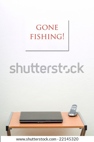 Gone Fishing sign on wall, office desk with closed laptop and phone
