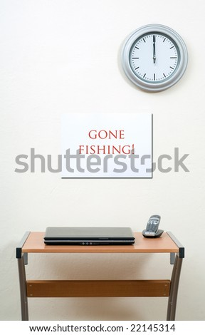 Gone fishing sign with office desk, laptop and clock