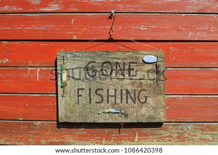 Gone Fishing Sign Written On A Wooden Plaque Hanging On A Weathered Wooden Fence. #1086420398
