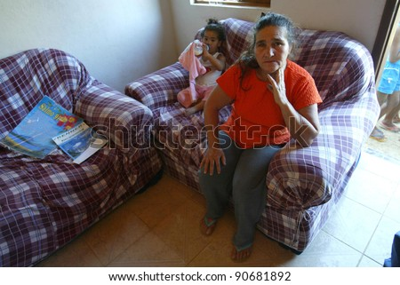 GONZAGA, BRAZIL - JULY 26:  Maria Otoni de Menezes sits in her home July 26, 2005 in Gonzaga, Brazil. Maria's son, Jean Charles de Menezes, 27-years-old, was killed by British undercover police. - stock photo