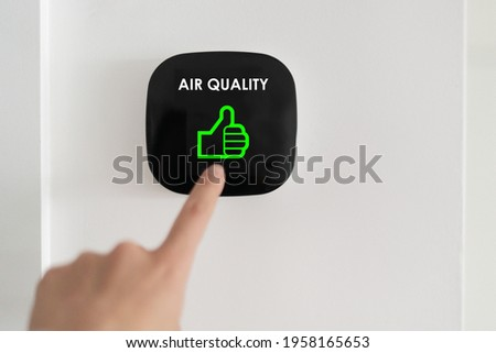 Good air quality indoor smart home domotic touchscreen system. air. Woman touching touchscreen checking air purifier filter at green level with thumbs up graphics.