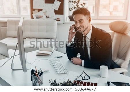 Good business talk. Handsome young man in formalwear talking on the phone and smiling while sitting at the office desk