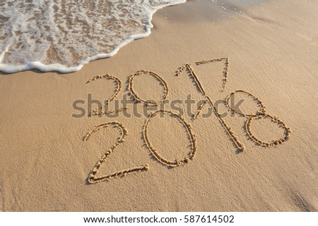 Good bye 2017 hello to 2018. Concept of upcoming new year and passing of time, handwritten on sandy coastline. #587614502