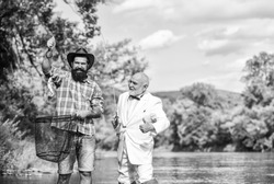 Good catch. Bearded men fishing. Family day. Lucky and skilled. Spinners and tackle. Nice catch. Bait and hook. Hobby and recreation. Catching fish with friend. Friends catch fish. Fellow fishermen.