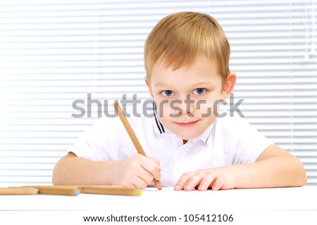 Good Caucasian male sitting at the table draws on a light background