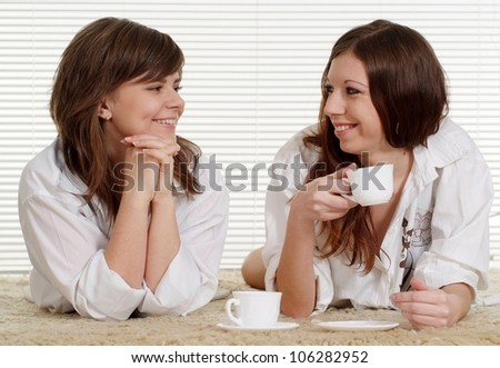 Good Caucasian two girls lying on the carpet with cups