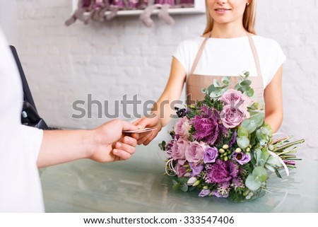 Good choice. Close up of credit card in hands of professional florist while getting it from client and doing her job