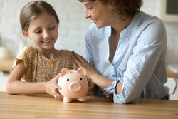 Good choice. Cropped shot of happy mom embracing little daughter with funny piggybank praise child for making wise decision to save pocket cash. Small kid girl plan to collect money for future needs