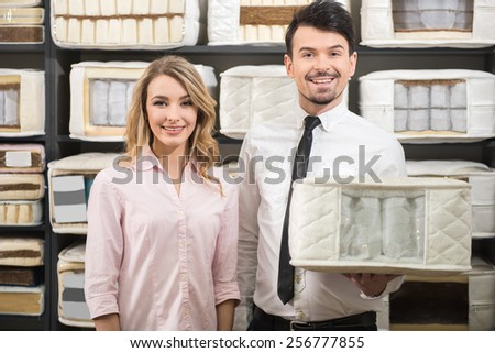 Good choice. The young salesman and the customer with quality mattresses in the store.