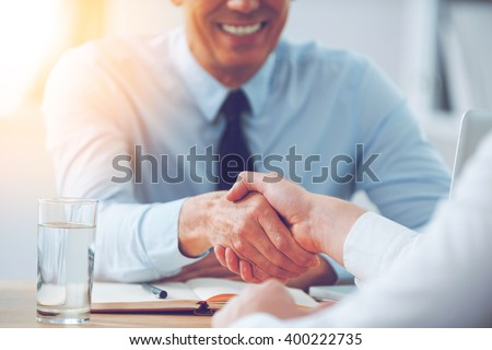 Good deal. Close-up of two business people shaking hands while sitting at the working place #400222735