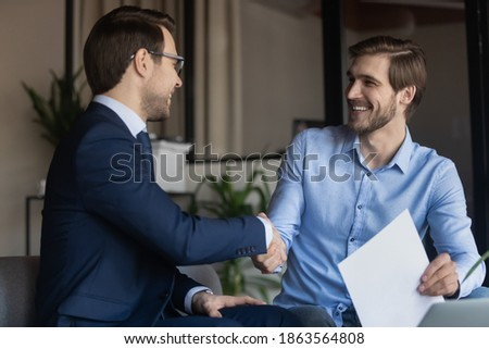 Good deal! Two business partners shaking hands after signing contract, client satisfied of getting loan insuring life handshaking with banker, happy job applicant appreciating hr for receiving place