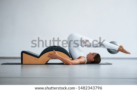 Good endurance needed. Confident young sporty woman with slim body type in the healthy center doing exercises by using special equipment.