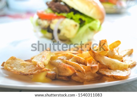 Good fresh crispy homemade fries with homemade hamburger in the background.