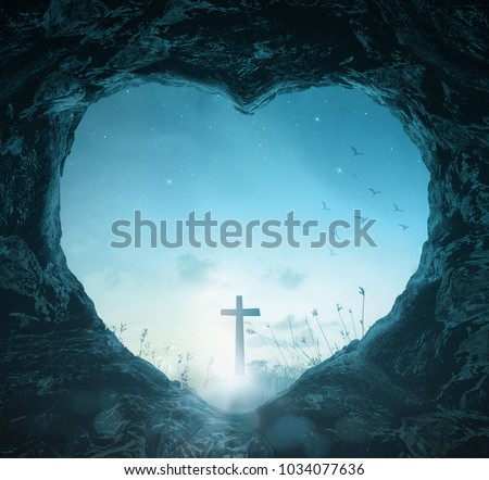 Good Friday concept: Heart shape of empty tomb stone with silhouette cross over meadow night background