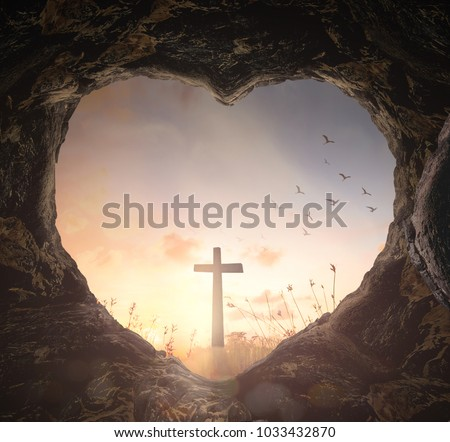 Good Friday concept: Heart shape of empty tomb stone with the cross over meadow sunrise background