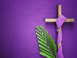 Good Friday, Lent Season and Holy Week concept - A religious cross and palm leaves on purple background.