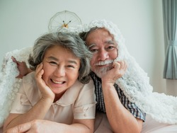 Good health mature couple smiling embracing health care lying In the bedroom, People lifestyle concept.