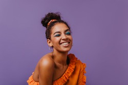 Good-humoured black girl funny smiling in studio. Ecstatic young woman in summer blouse chilling on purple background.