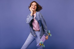 Good-humoured laughing woman in jeans dancing on violet background. Photo of magnificent caucasian girl with skateboard.