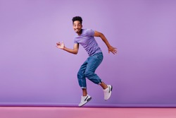 Good-humoured male model dancing in new white sneakers. Studio shot of ecstatic african guy in jeans.