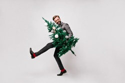Good-humoured office worker dancing after party. Indoor shot of caucasian man holding christmas tree.