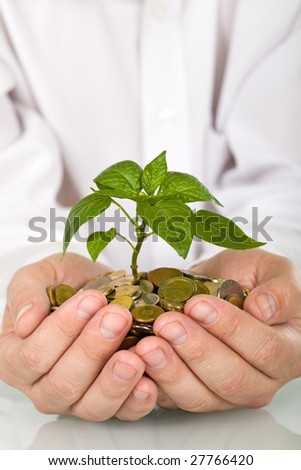 Good investment and money making concept - businessman hands holding plant sprouting from a handful of coins